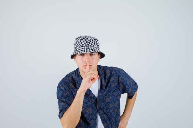 Młody chłopak pokazując gest ciszy, trzymając rękę na talii w białej koszulce, kwiecistej koszuli, czapce i patrząc poważnie, widok z przodu.