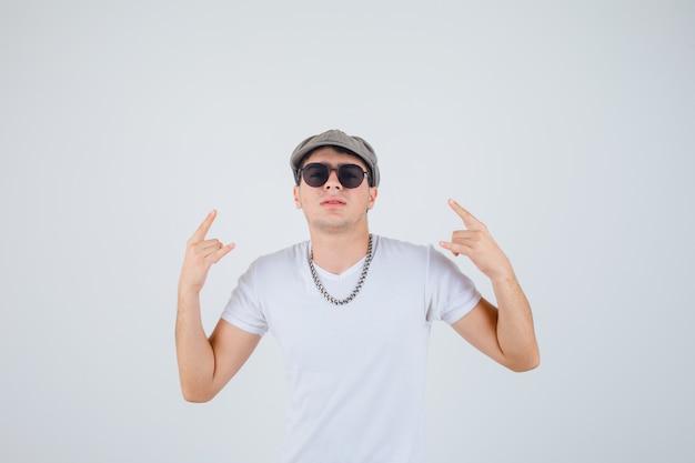 Młody chłopak pokazując gest rocka w t-shirt, kapelusz i patrząc pewny siebie, widok z przodu.