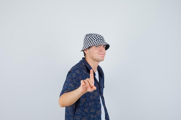 Młody chłopak pokazując trzymanie na minutowym geście w białej koszulce, kwiecistej koszuli, czapce i patrząc szczęśliwy, widok z przodu.
