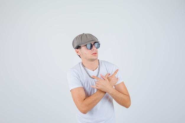 Młody chłopak pokazujący rockowy gest, wskazujący na obie strony w koszulce, czapce i fajnie wyglądający. przedni widok.