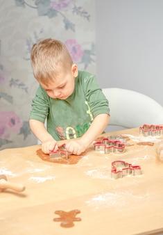 Młody chłopak popycha piernikowe kształty. przygotowuję się do świąt.