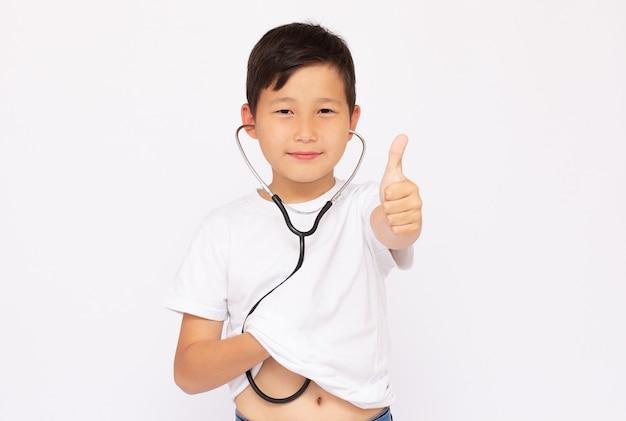 Młody chłopak próbuje słuchać, jak jego serce bawi się stetoskopem