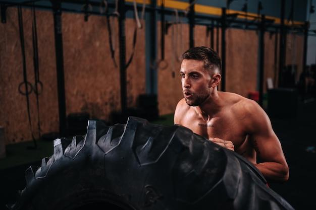 Młody chłopak rasy kaukaskiej po trzydziestce, który podnosi koło, aby wykonywać ćwiczenia
