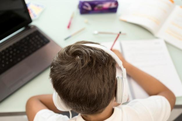 Młody chłopak robi swoją pracę domową widok z tyłu