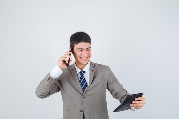 Młody chłopak rozmawia z telefonem, patrząc na kalkulator w oficjalnym garniturze i wygląda na szczęśliwego. przedni widok.