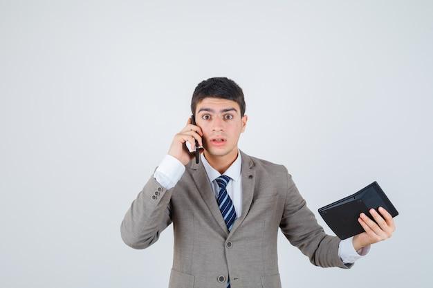 Młody chłopak rozmawia z telefonem, trzymając kalkulator w oficjalnym garniturze i wyglądający na zszokowanego. przedni widok.