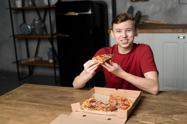 Młody chłopak siedzący przy stole z uśmiechem trzyma w rękach kawałek pizzy
