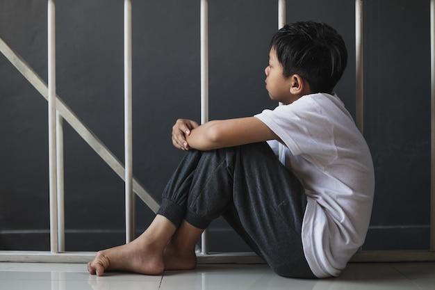 Młody chłopak siedzący samotnie ze smutnym uczuciem w domu