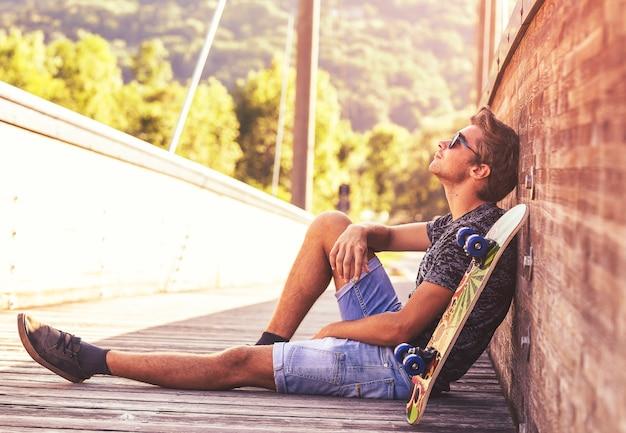 Młody chłopak siedzi na drewnianym moście z jego deskorolka.