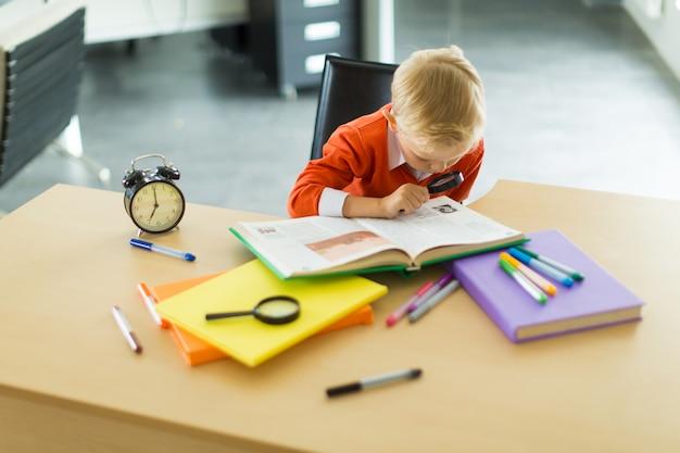 Młody chłopak siedzi przy biurku w biurze, przytrzymaj szkło powiększające