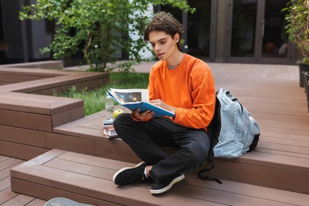Młody chłopak siedzi z dużym plecakiem i w zamyśleniu czytając książkę na dziedzińcu uniwersytetu