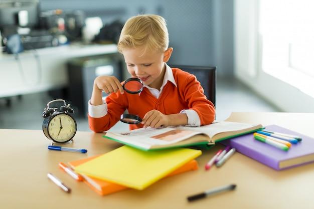 Młody chłopak siedzieć przy biurku w biurze, trzymać lupę