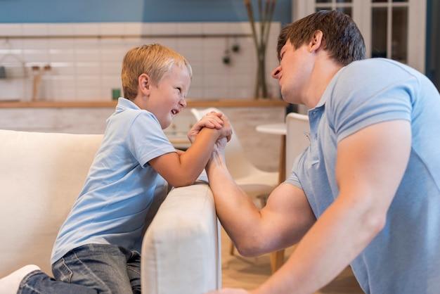 Młody chłopak siłowanie się na rękę z ojcem