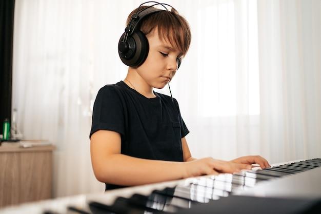 Młody chłopak sitiing na pianino cyfrowe. gra na klawiaturze, skupiony dzieciak ma aktywność w domu. hobby
