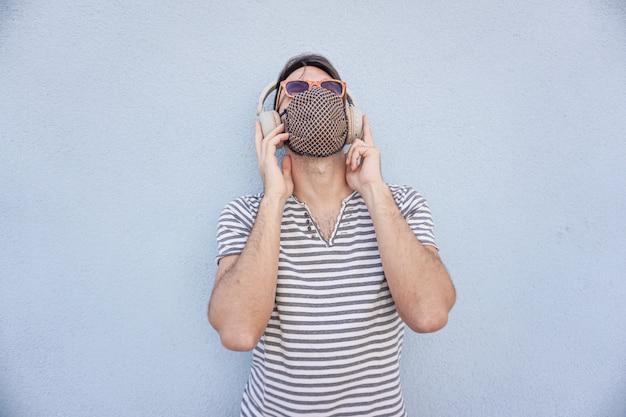 Młody chłopak słuchanie muzyki z maską