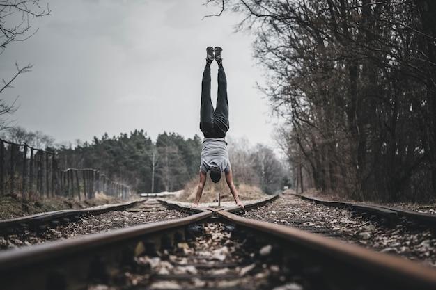 Młody chłopak stoi razem na rękach na nogach szyn kolejowych