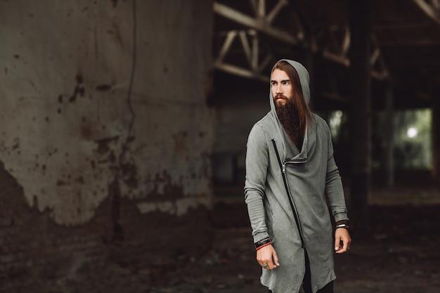 Młody chłopak stoi w opuszczonym budynku. wędrujący chłopiec facet jest ubrany w stylowe ciuchy, ma długą brodę.