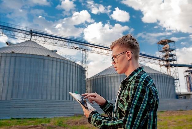 Młody chłopak stoi z tabletem w pobliżu metalowej windy na rolniczym terenie. magazyn zboża.