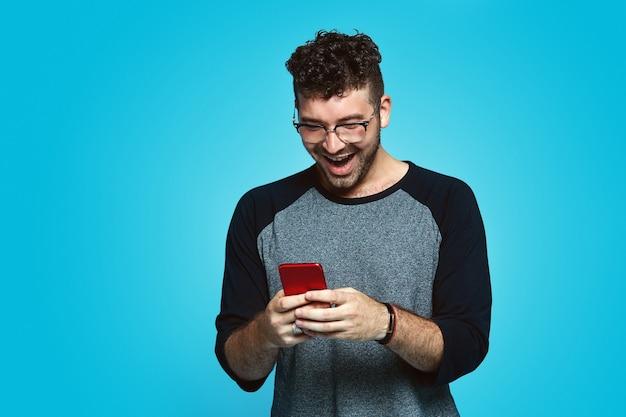 Młody chłopak szczęśliwie patrząc na ekran smartfona na białym tle nad niebieską ścianą
