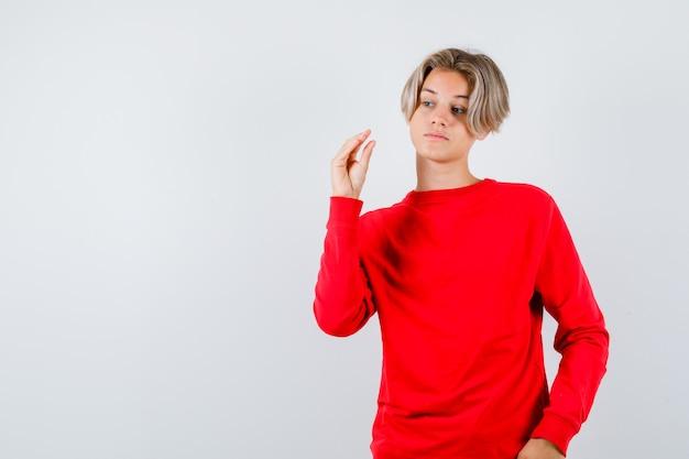 Młody chłopak teen pokazano gest bla-bla-bla w czerwonym swetrze i patrząc sarkastycznie. przedni widok.
