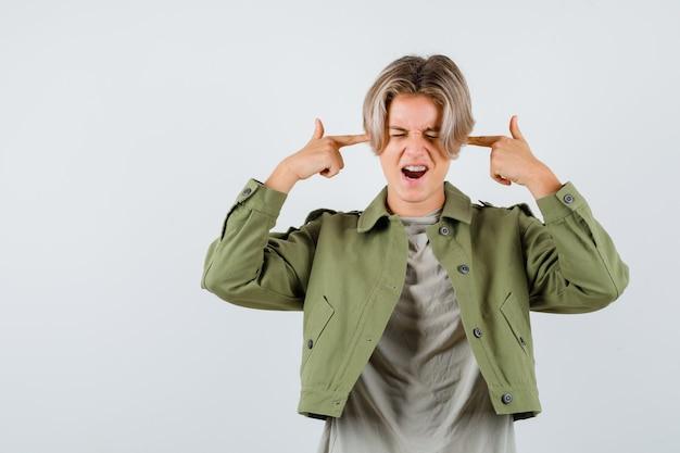 Młody chłopak teen pokazano gest samobójstwa w koszulce, kurtce i patrząc zdecydowany. przedni widok.