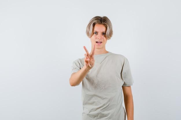 Młody chłopak teen pokazano gest zwycięstwa w t-shirt i patrząc pewnie, widok z przodu.