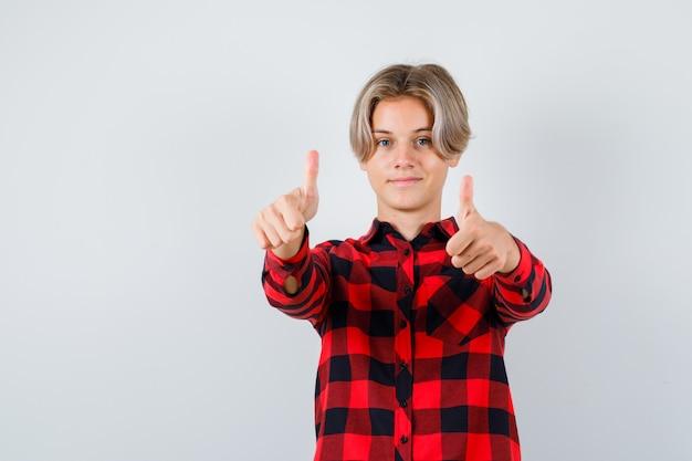 Młody chłopak teen pokazano podwójne kciuki w kraciastej koszuli i patrząc wesoły, widok z przodu.