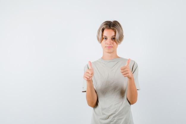 Młody chłopak teen pokazuje podwójne kciuki w t-shirt i wygląda pewnie. przedni widok.