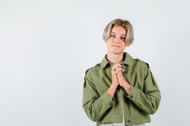 Młody chłopak teen, ściskając ręce w geście modlitwy w zielonej kurtce i patrząc z nadzieją. przedni widok.