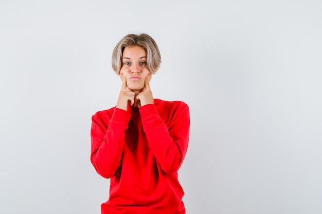 Młody chłopak teen trzymając palce na policzkach w czerwonym swetrze i ponury. przedni widok.