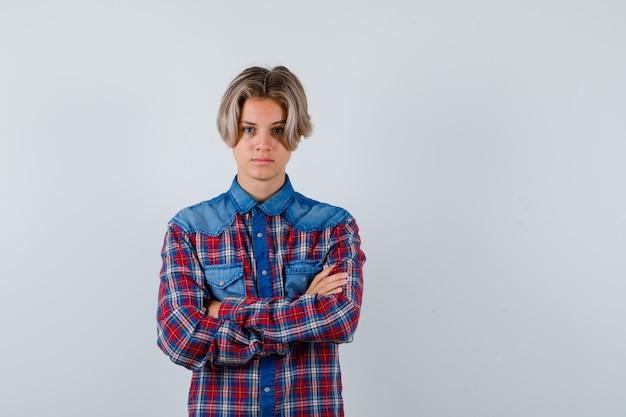 Młody chłopak teen trzymając ręce złożone w kraciastej koszuli i patrząc poważnie. przedni widok.