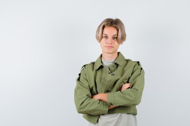 Młody chłopak teen trzymając ręce złożone w t-shirt, kurtkę i patrząc pewnie, widok z przodu.