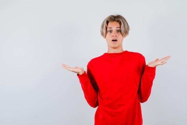 Młody chłopak teen w czerwonym swetrze pokazując bezradny gest i patrząc zdziwiony, widok z przodu.