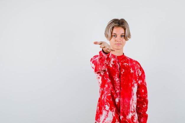Młody chłopak teen w koszuli, rozciągając rękę na aparat i patrząc wesoły, widok z przodu.