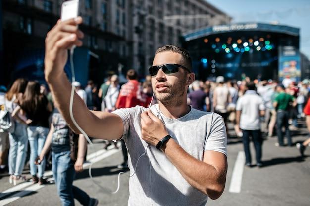 Młody chłopak to relacja z wydarzenia sportowego lub koncertu. bloger używa smartfona do uruchomienia. dziennikarz to powołanie