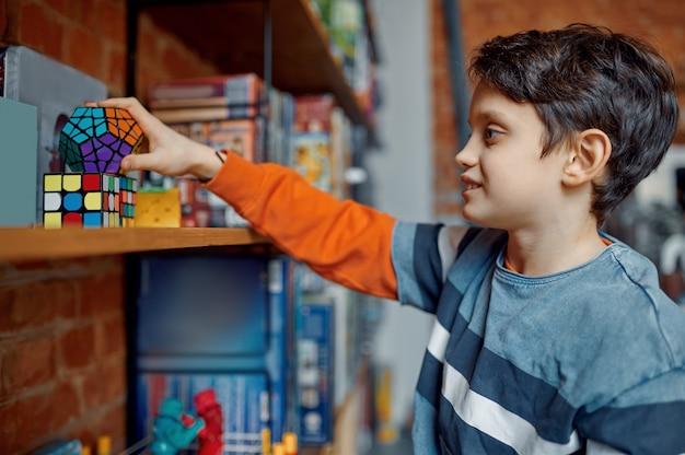 Młody chłopak trzyma w ręku kolorową kostkę układanki. zabawka do treningu mózgu i logicznego umysłu, kreatywna gra, rozwiązywanie złożonych problemów