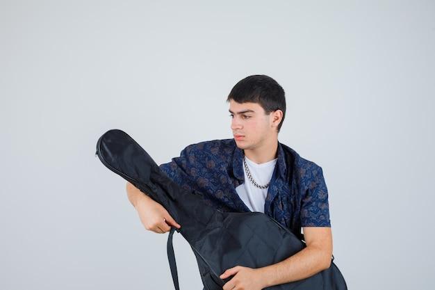 Młody chłopak trzymając gitarę, patrząc z boku w t-shirt i patrząc skupiony. przedni widok.