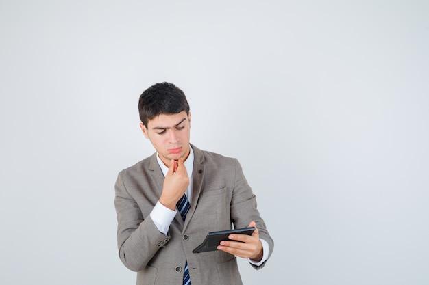 Młody chłopak trzymając kalkulator, kładąc rękę na brodzie w oficjalnym garniturze i patrząc zamyślony, widok z przodu.
