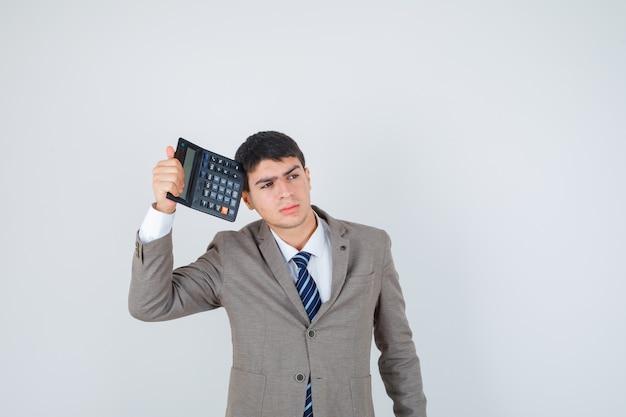 Młody chłopak trzymając kalkulator, myśląc o czymś w formalnym garniturze i patrząc zamyślony, widok z przodu.