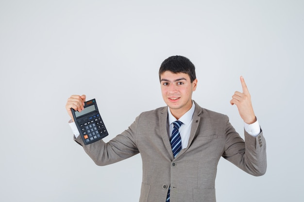 Młody chłopak trzymając kalkulator, podnosząc palec wskazujący w geście eureki w formalnym garniturze i wyglądający rozsądnie. przedni widok.