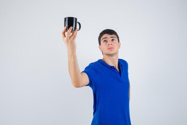 Młody chłopak trzymając kubek, patrząc na to w niebieskiej koszulce i patrząc poważnie. przedni widok.