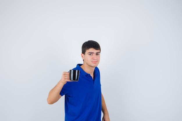 Młody chłopak trzymając kubek, uśmiechając się w niebieskiej koszulce i patrząc szczęśliwy, widok z przodu.