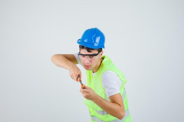 Młody chłopak trzymając szczypce w mundurze budowy i patrząc skoncentrowany. przedni widok.