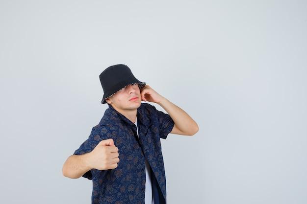 Młody chłopak trzymający jedną rękę w pobliżu ucha, zaciskając pięść, pozując w białej koszulce, kwiecistej koszuli, czapce i patrząc pewnie na siebie, patrząc z przodu.