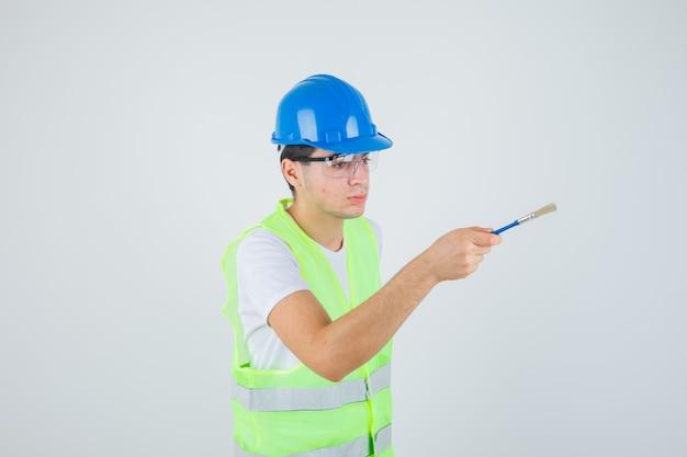 Młody chłopak trzymający pędzel, próbujący dać go komuś w mundurze budowlanym i wyglądający na skupionego. przedni widok.