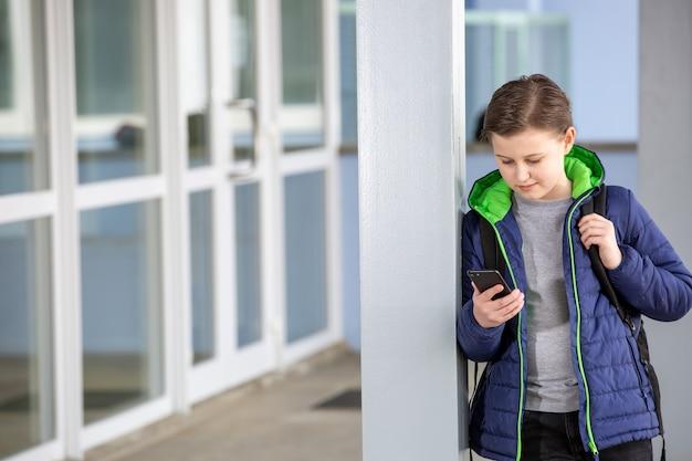 Młody chłopak trzymający się z dala od szkoły i grający w gry na telefonie komórkowym, nieobecność w szkole