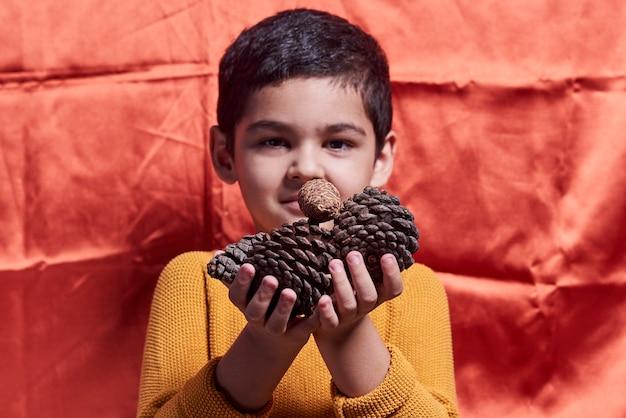 Młody chłopak trzymający szyszki na pomarańczowym tle