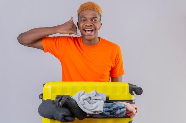 Młody chłopak ubrany w pomarańczową koszulkę stojącą z walizką podróżną pełną ubrań optymistycznie i wesoło uśmiechając się, dzwoniąc do mnie gestem nad białą ścianą
