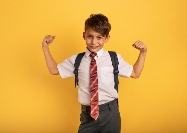 Młody chłopak uczeń zachowuje się jak umięśniony mężczyzna. żółte tło