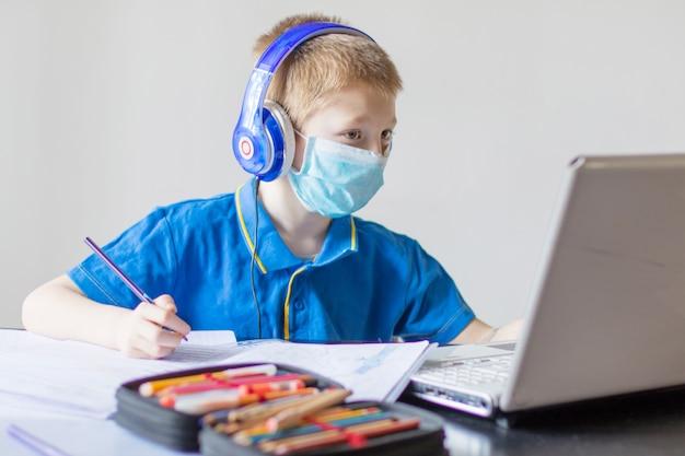 Młody chłopak uczy się matematyki podczas lekcji online w domu